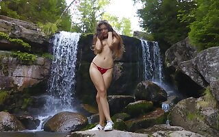Wide hipped Latina teen with a broad in the beam ass posing half naked by the waterfall